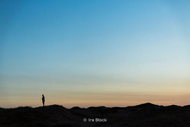 Silhouette of a man standing on hill in the South Gobi Desert, Mongolia.  In the Khongoryn Els sand dunes in Gobi Gurvansaikh...