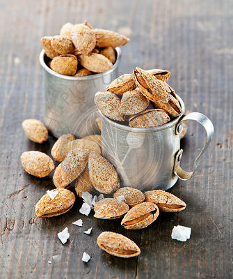 Roasted  salted almonds on wooden background
