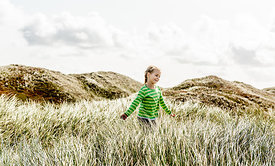Danish girl playing in the dunes in Thy
