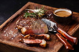 Sliced grilled meat steak New York Striploin with Pepper sauce and knife and fork on wooden board on black background
