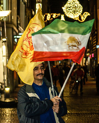 Amsterdam, Netherlands 2015-01-08: Man carrying two flags at the demonstration of support for Charlie Hebdo.