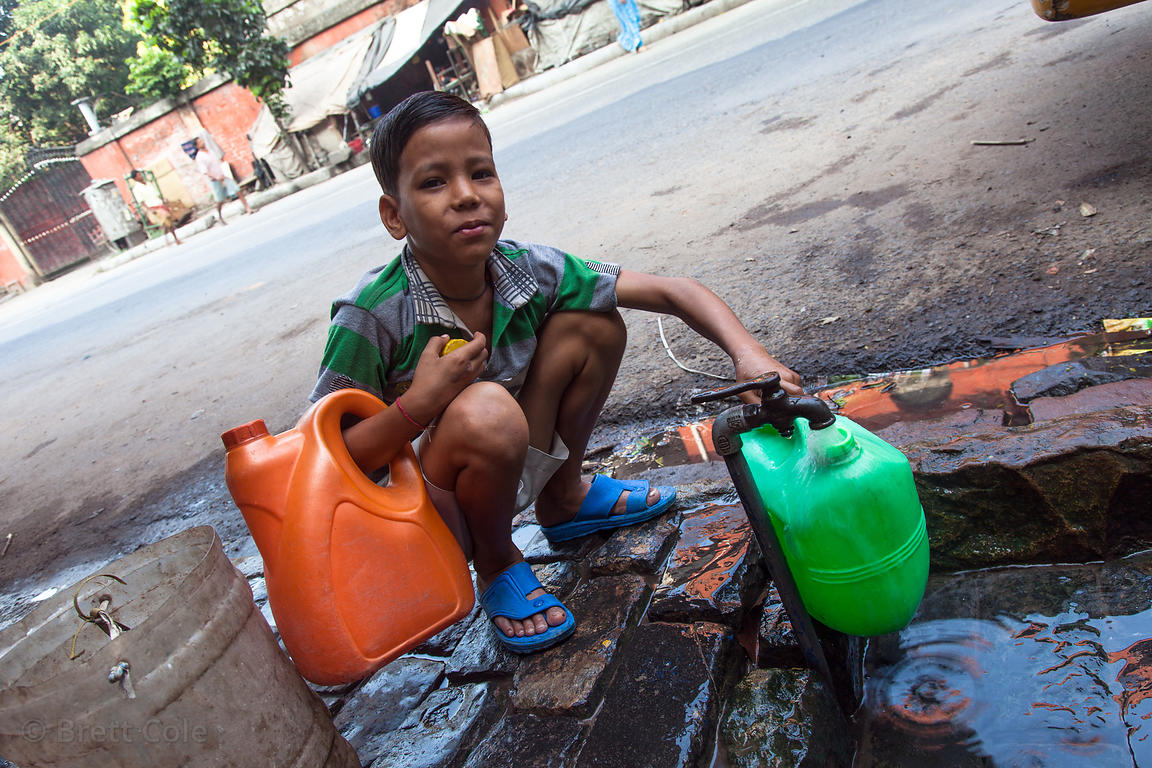 A boy fills water jugs at a public spigot in Howrah, sister city to Kolkata, India.
