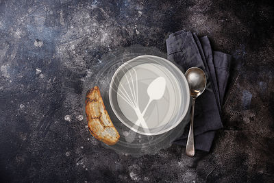 Vichyssoise cold cream soup in bowl with bread on dark background copy space