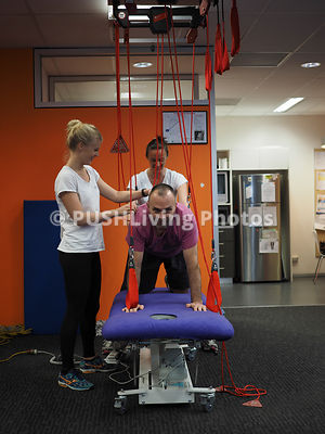 Two Female Physical Therapists Giving Treatment To A Man With A Disability