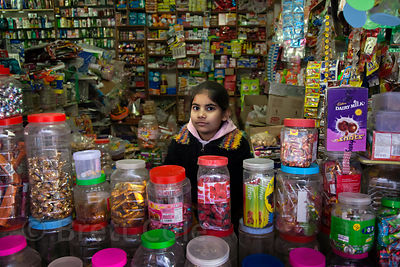 A girl sits in an incredibly crowded shop in Pushkar, Rajasthan, India