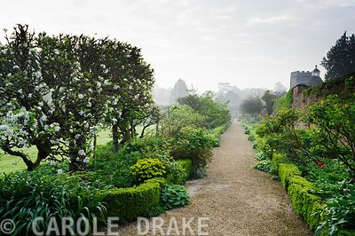 Walled Garden features gravel paths, box hedging, beds of herbaceous perennials and espaliered apple trees. Rousham House, Bi...