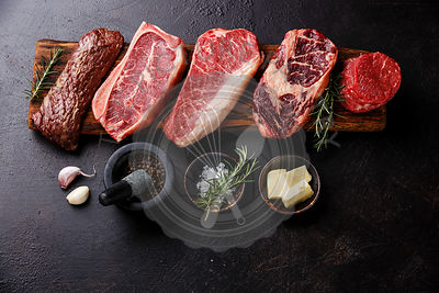 Variety of Raw Black Angus Prime meat steaks Machete, Blade on bone, Striploin, Rib eye, Tenderloin fillet mignon on wooden b...