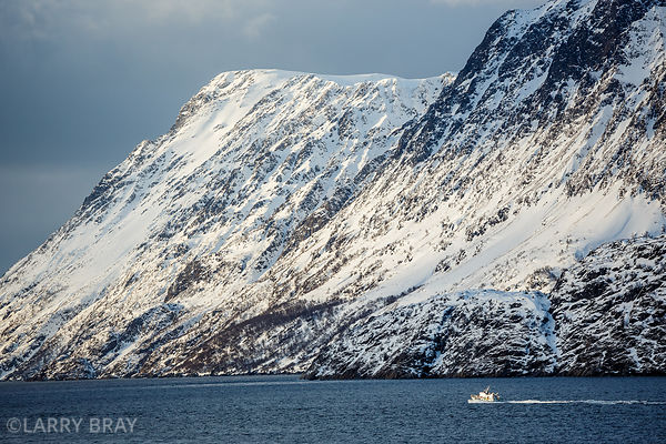 Small boat set against steep snowy sides of fjord in Norway