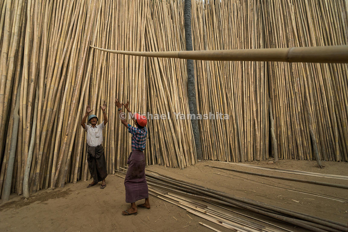 Workers stack poles at an outdoor bamboo market in Myin Kaba, a village outside Bagan. The settlement is known for selling ba...