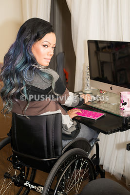Young professional woman in a wheelchair working on her computer