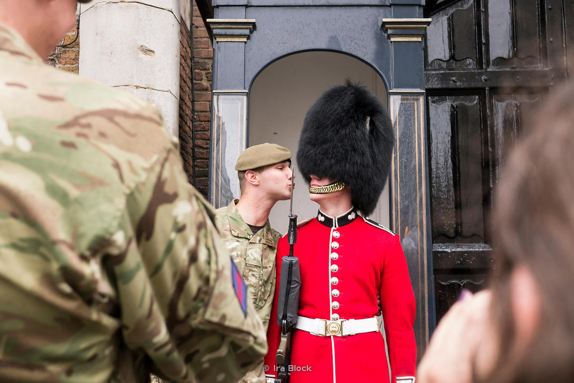 Army soldiers playing a joke and taking photographs with a Queen's Guard.