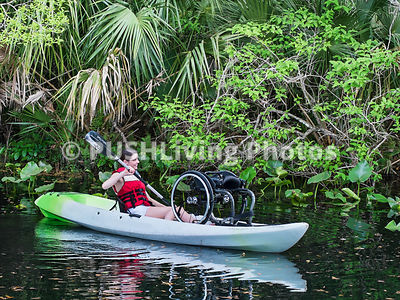 Young woman using a wheelchair kayaking on a river