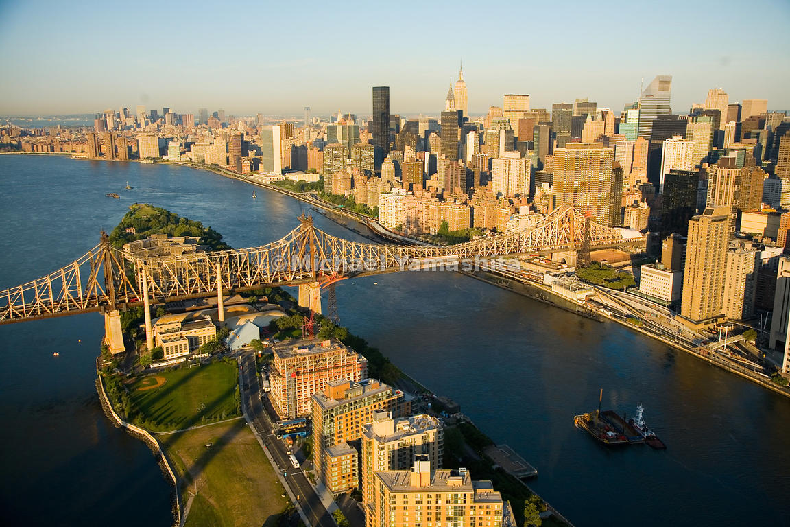 The Queensborough Bridge spans the East River and crosses over Roosevelt Island, connecting Manhattan to Long Island City, in...