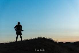 Silhouette of a man with a camera standing on hill in the South Gobi Desert, Mongolia.  In the Khongoryn Els sand dunes in Go...
