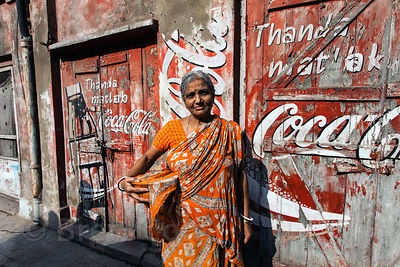 A woman stands near a weathered Coke banner in the Sovabazar area of Kolkata, India.