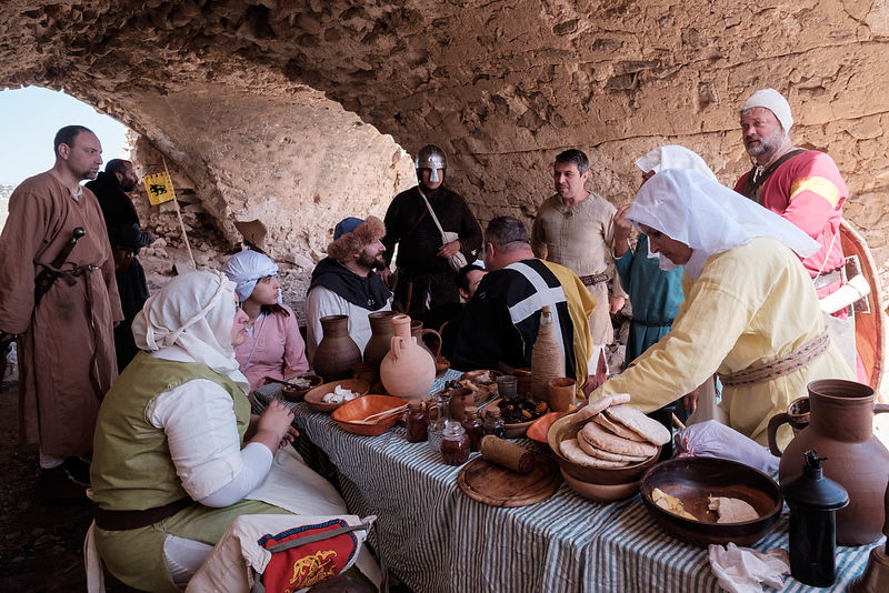 History enthusiasts dressed in costumes sit next to a table during an event to relive the experiences of pilgrims who travell...