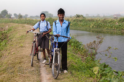 A brother and sister bike home from school on a trail in the East Kolkata Wetlands, Kolkata, India.