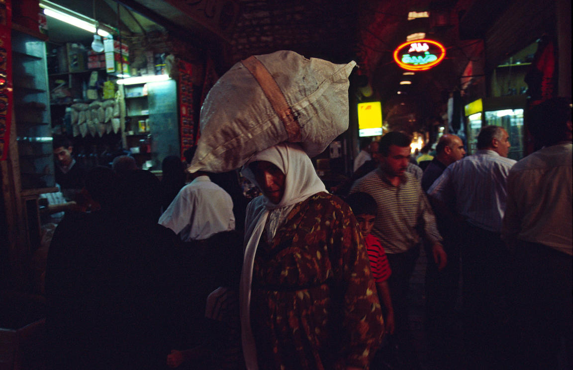 Syria - Aleppo - A woman carries a sack on her head in the Souk