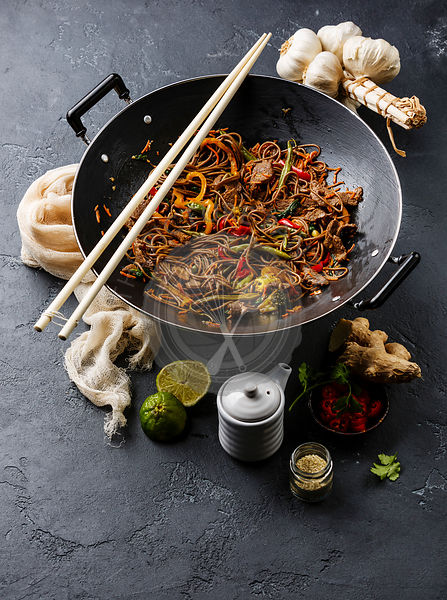 Asian fast food Stir fry noodles soba with beef and vegetables in wok pan on dark stone background