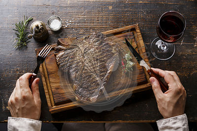 Grilled T-bone steak on serving board, fork and knife in male hands and red wine on wooden table background