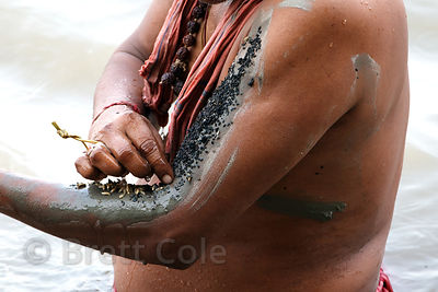 A man places seeds and grains on mud from the Ganges river on his arm, in observance of Mahalaya, a tribute to deceased relat...