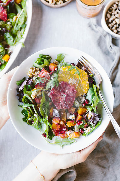 A woman is holding a large plate of Citrusy Roasted Beet Goat Cheese Salad with Black Eyed Peas.