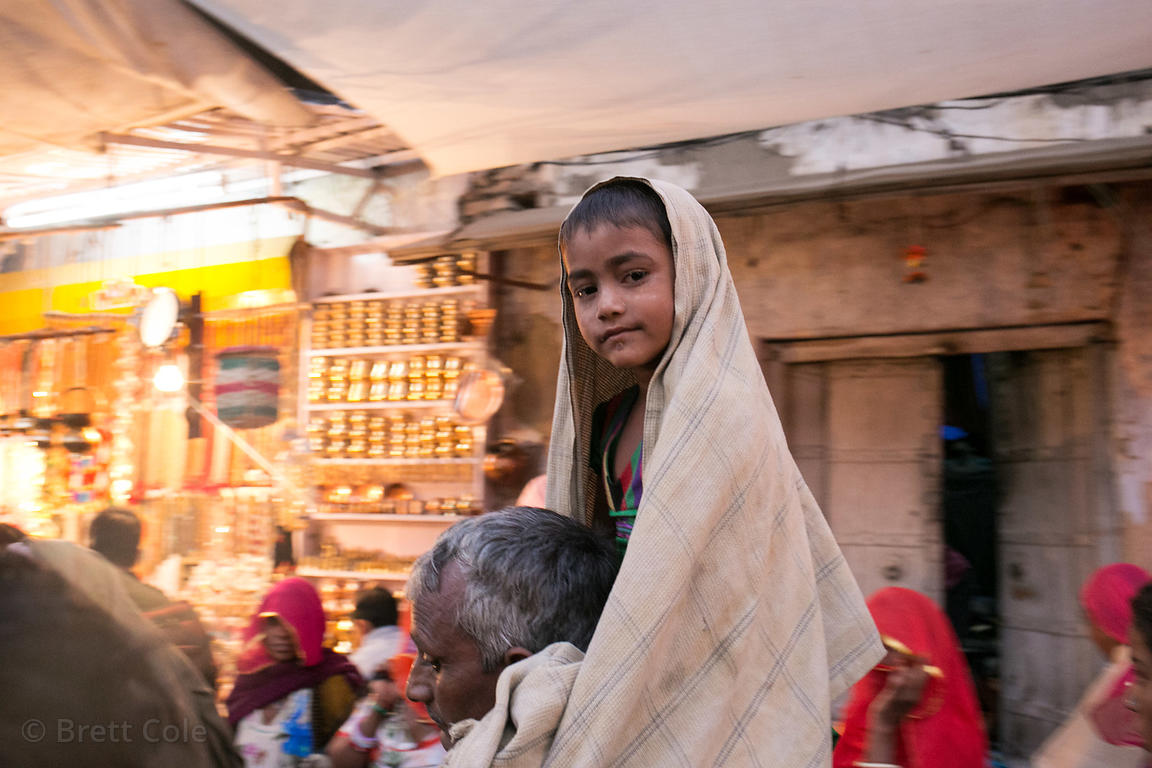 A boy rides on his father's shoulders in a market in Pushkar, Rajasthan, India