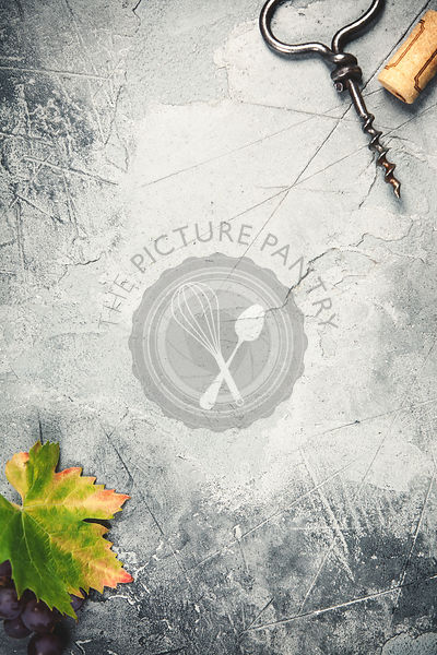 Top view of an old cork screw and grape leaf on gray concrete background with space for text.  A vertical design template for...