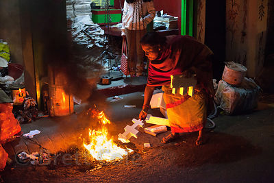 A woman in the Lord's More neighborhood of Kolkata, India burns a pile of polystyrene styrofoam, letting of a cloud of black ...
