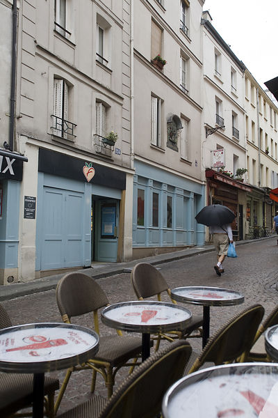 France - Paris - A man with an umbrella walks up Rue Moufftard in the rain with his shopping