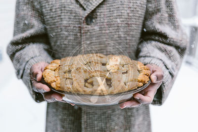 A man is photographed as he is holding an apple pie while it is snowing outside.