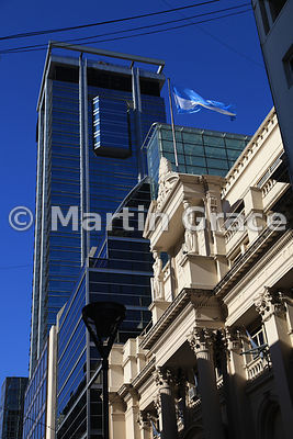 Stone building of the Central Bank of the Argentine Republic, Buenos Aires flying Argentine flag contrasted with modern skysc...