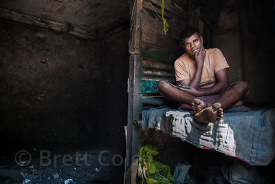 A man sleeps in a bunk in a small factory where he breaks up pieces of coal, near Metiabruz, Kolkata, India.