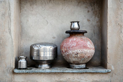 Metal drinking water cups and clay pot form a still life in a window sill, Kharekhari village, Rajasthan, India