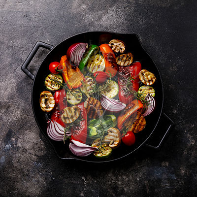 Grilled assorted vegetables in cast iron pan on dark background
