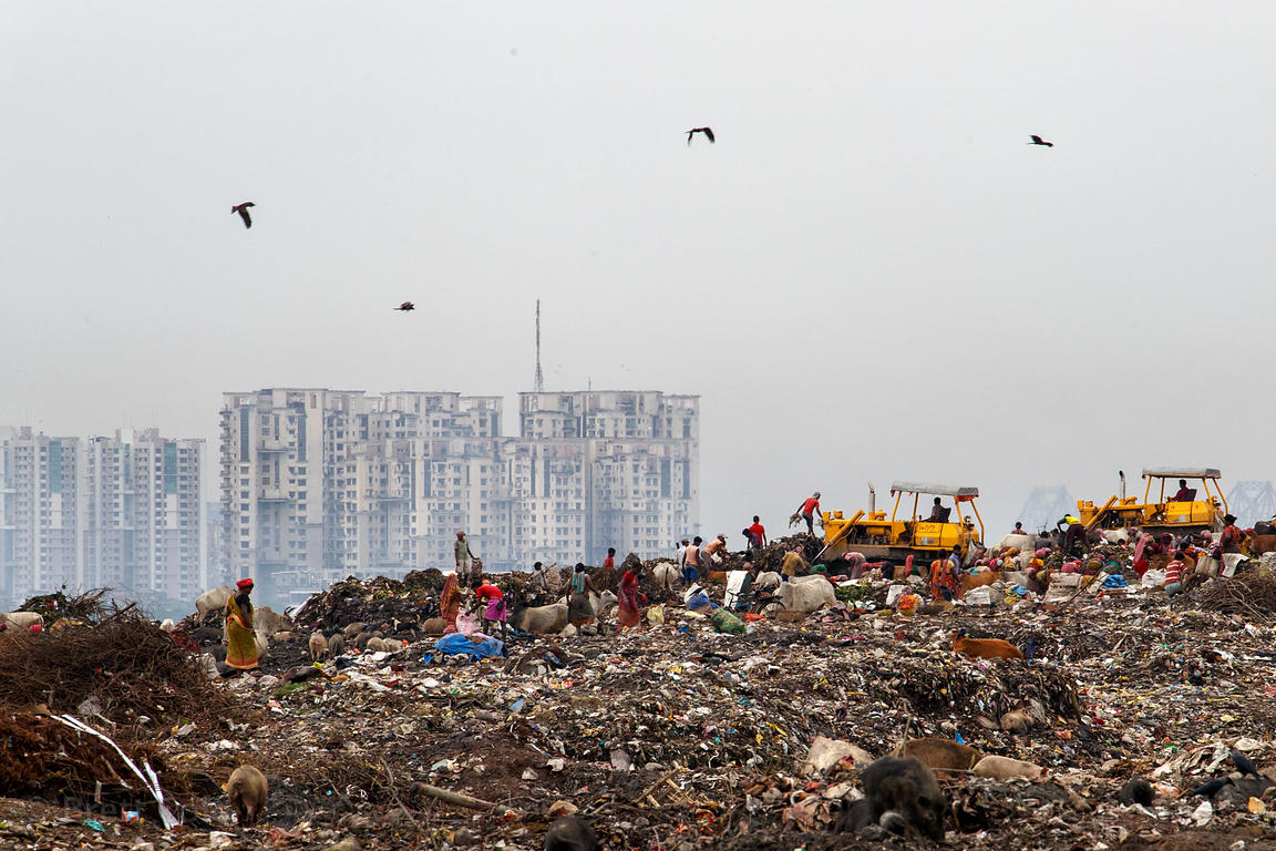 Workers atop the 100 foot tall Dhapa dumping ground (landfill), Dhapa, Kolkata, India. Dhapa is a large industrial zone that ...