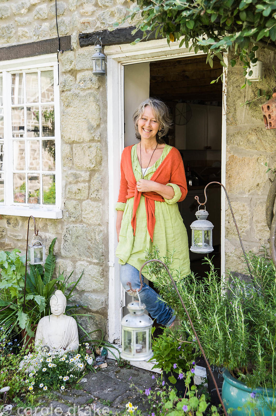 Brigit Strawbridge at the door of her rented cottage in the historic Pump Yard, St James', Shaftesbury, surrounded by plants.
