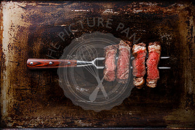 Slices of grilled meat barbecue steak Rib eye on meat fork on dark metal background