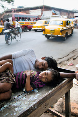 A man and his daughter sleep on a street in Howrah, sister city to Kolkata, India.