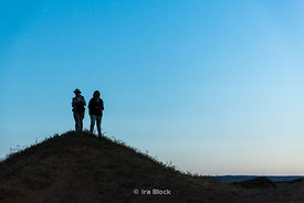 Silhouette of two people standing on hill in the South Gobi Desert, Mongolia.  In the Khongoryn Els sand dunes in Gobi Gurvan...