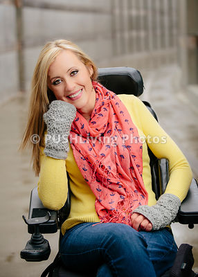 Womam in a power wheelchair in a riverside park during fall.