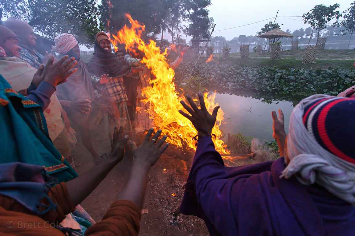 Fishermen gather around a fire on a cold winter morning, in the town of Chingrihata, East Kolkata Wetlands, Kolkata, India.