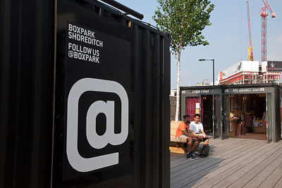 UK - London - Two fashionable young men sit and talk on the roof of the Boxpark - a so-called 'pop up mall' comprising of old...