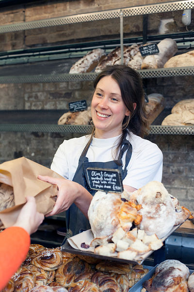 UK - London - A woman serving a customer at the Fabrique Bakery