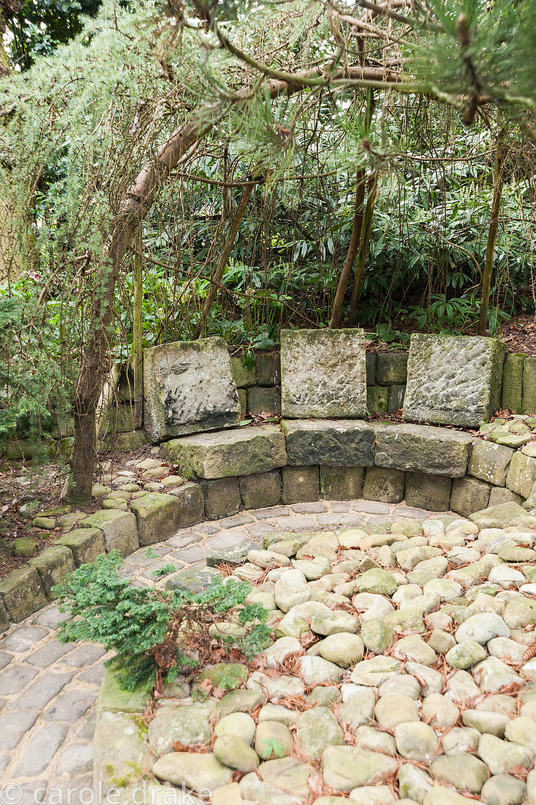 Stone seats below a larch arbour with oval detailing set into the paving. York Gate Garden, Adel, Leeds, Yorkshire