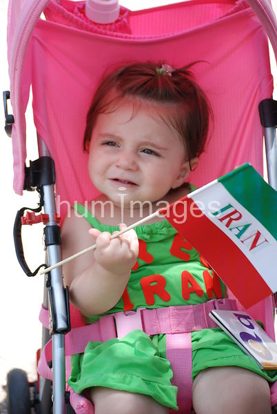Toddler holding Iran flag at protest rally in stroller