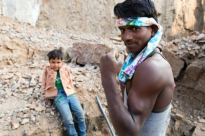 Strong worker and his son at a family run rock mine near Tilora village, Rajasthan, India