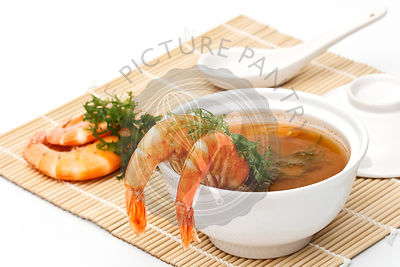 Served place setting asian style with spicy Shrimp Soup on white background