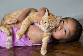Asian Girl Holding an Orange Tabby Cat