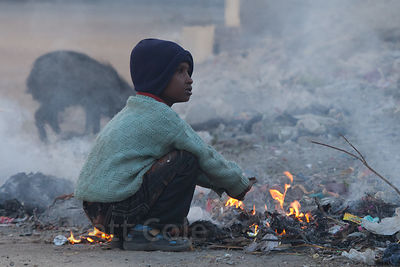 A boy warms himself by a fire in the streets of Pushkar, Rajasthan, India